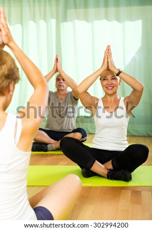 Young  yoga instructor showing asana to senior attenders - stock photo