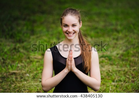 Young yoga teacher practicing outdoors in a park over green grass with copy space - stock photo