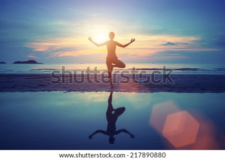 Young yoga woman meditation on the beach at sunset. - stock photo