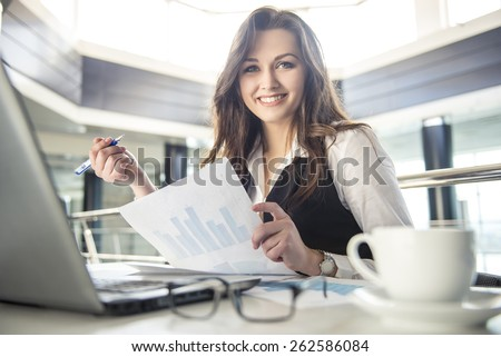 Younge beautiful business woman working with documents in the office - stock photo