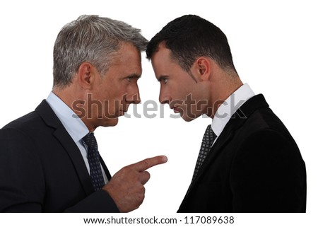 Younger and older businessmen head to head - stock photo