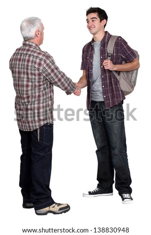 Younger and older men shaking hands - stock photo
