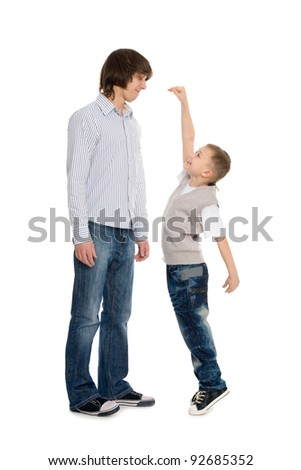 Younger brother of measuring the growth of an older brother. - stock photo