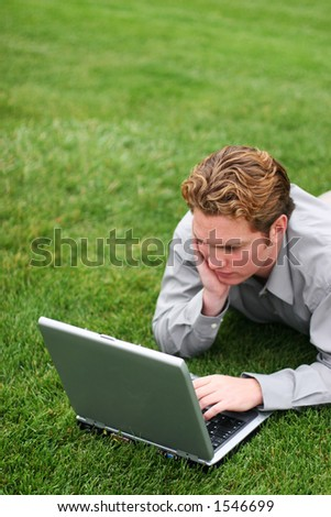 Younger businessman in gray shirt relaxes in the green grass as he looks at his laptop screen - stock photo