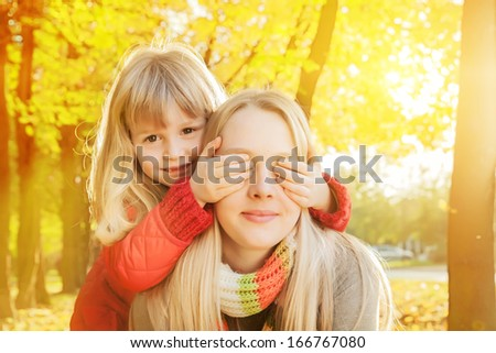 Younger sister standing behind older sister, covering her eyes in autumn's colorful park - stock photo