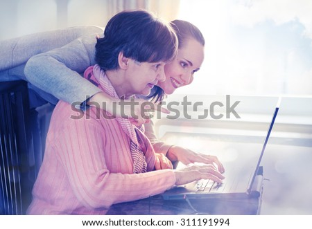 Younger woman helping an elderly person using laptop computer for internet search. Young and pension age generations working together. - stock photo