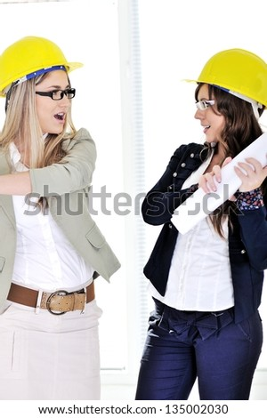 Youngr co-worker getting ready to hit her co-worker with a set of architectural plans - stock photo