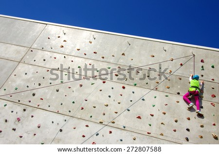 Youngster's effort in climbing a wall to reach the top - stock photo