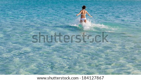 Younh woman is running in the sea
