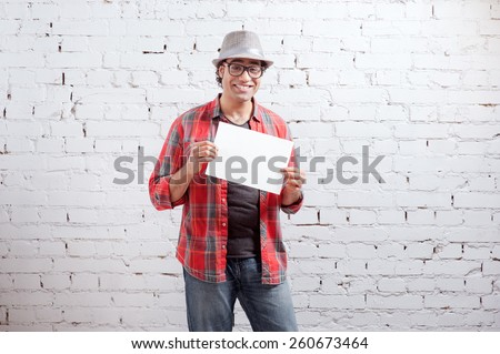 Your advertisement in good hands. Handsome young Arabic man holding copy space while standing against brick wall. - stock photo