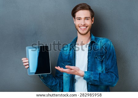 Your advertisement on his digital tablet. Smiling young man holding digital tablet and pointing at it while standing against grey background - stock photo