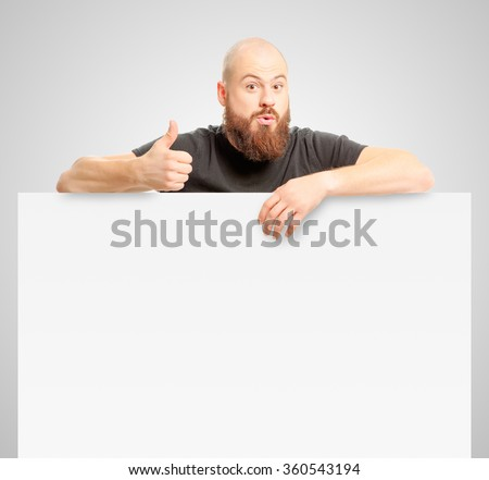 Your advertising below.Amazed bearded man showing thumb up and leaning at copy space while standing against white background - stock photo
