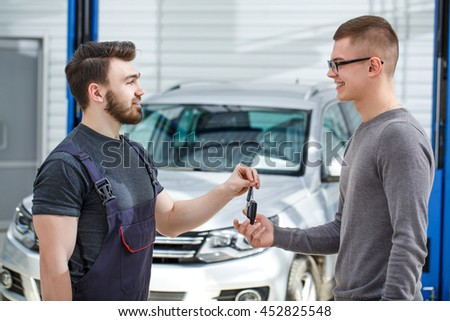 Your car is perfect now. Shot of a car mechanic passing car keys to the car owner after repairing his vehicle - stock photo