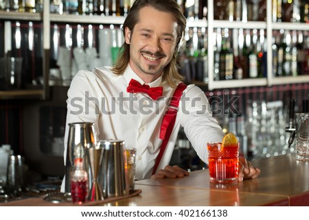 Your drink is ready. Waist up shot of a happy good-looking bartender presenting a cocktail.