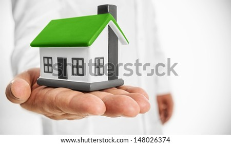 Your Eco house -House with a green roof in hand businessman - stock photo