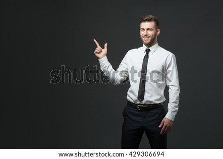 Your logo or product goes here! Studio shot of handsome young businessman holding his arm up presenting copyspace. - stock photo