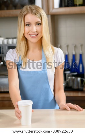 Your order. Pleasant positive glad waitress holding cup of coffee and giving it to you while standing at a counter
