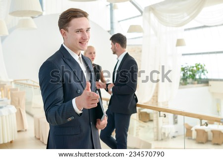 Your success in business. Smiling businessman points his finger while his colleague businessmen standing and talking in the background - stock photo