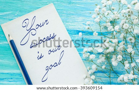 Your Success Is Our Goal Inspirational quote women's hand lettering for posters writing notebook note turquoise wooden background Word refer news, current affairs, special occasions business planning - stock photo