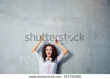 Your text here. Amazed beautiful young woman with curl hair pointing up while standing against grey wall. - stock photo