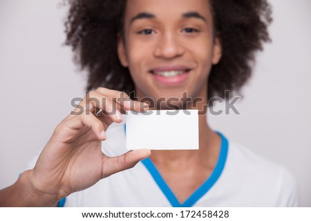 Your text here. Cheerful African teenager holding plastic card and smiling at camera while standing isolated on grey background - stock photo
