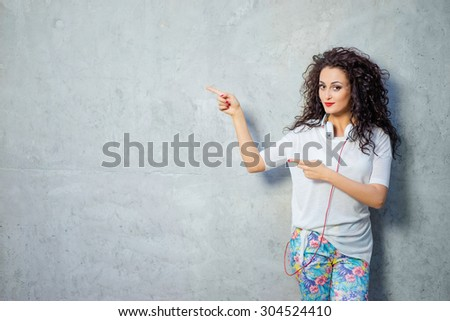 Your text here. Cheerful beautiful young woman with curl hair pointing away while standing against grey wall. - stock photo