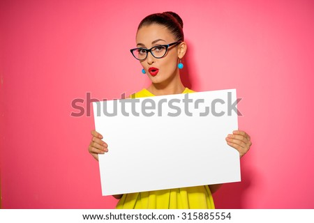 Your text here. Pretty young excited woman holding empty blank board. Colorful studio portrait with pink background. - stock photo