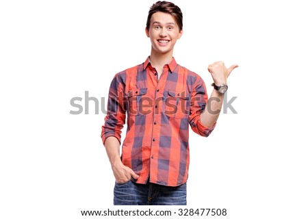 Your text here. Studio portrait of happy handsome young man pointing copy space with thumb up. Isolated on white. - stock photo
