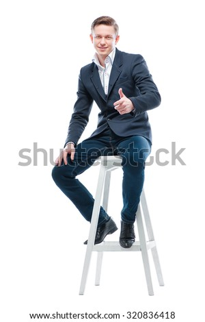 Youth and confidence. Attractive young man showing thumb up while sitting on chair. Isolated on white. - stock photo