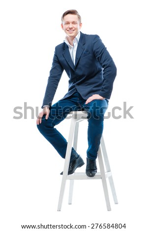 Youth and confidence. Attractive young man sitting on chair. Isolated on white. - stock photo