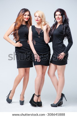 Youth and fashion. Three sexy chic young women in little black dresses standing arm in arm showing off their long shapely slender legs. Isolated on white.