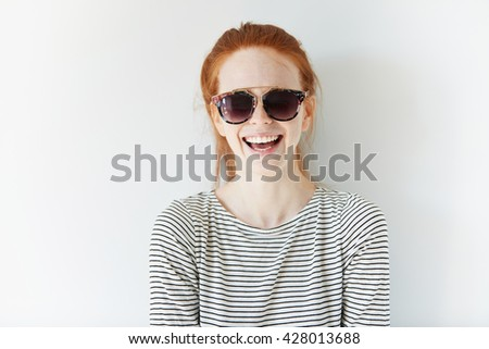 Youth and happiness concept. Portrait of happy attractive stylish young female in trendy clothes and hipster shades, laughing and having fun while posing isolated against white studio wall background - stock photo