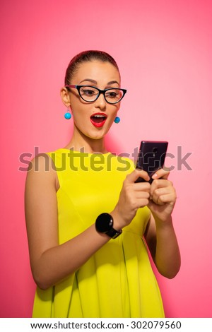 Youth and technology. Amazed young woman with smartwatch using mobile phone. Colorful studio portrait. Pink background. - stock photo
