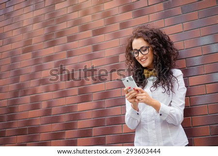 Youth and technology. Attractive young woman in shirt and bowtie using smartphone and smiling while standing against brick wall. - stock photo
