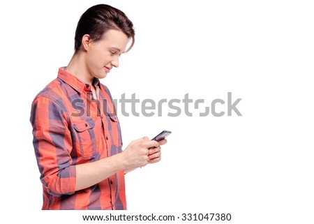 Youth and technology. Studio portrait of handsome young man using smart phone. Isolated on white.