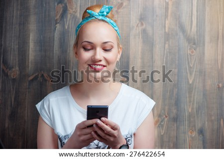 Youth and technology. Texting message. Attractive young blonde woman using smartphone against wooden background. - stock photo