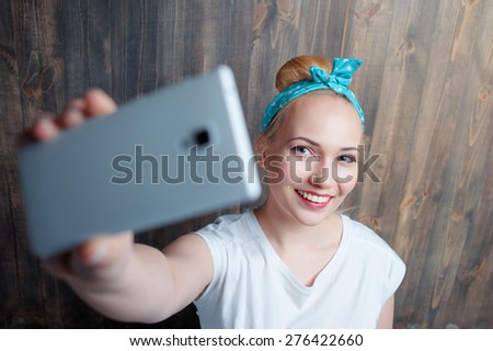 Youth and technology. Young attractive smiling woman taking selfie by smart phone against wooden wall. - stock photo