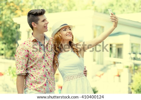 Youth and technology. Young smiling loving couple taking selfie on smartphone while standing in park. yellow tone