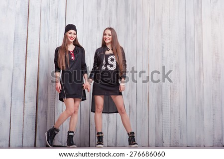 Youth and urban fashion. Attractive twins sisters. Two beautiful smiling young women standing together. - stock photo