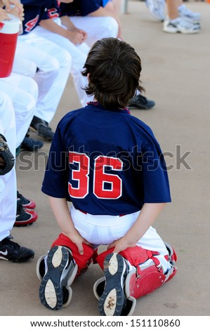 Youth baseball catcher sitting in dugout. - stock photo
