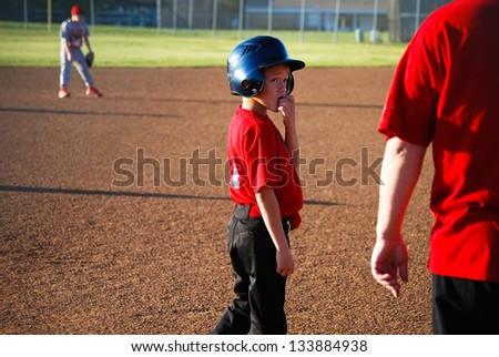 Youth baseball player looking back at coach. - stock photo