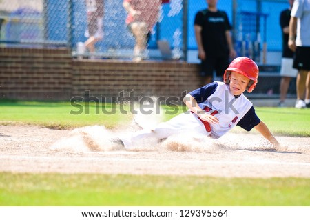 Youth baseball player sliding in at home. - stock photo