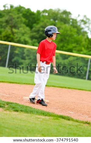 Youth baseball player standing on third base.