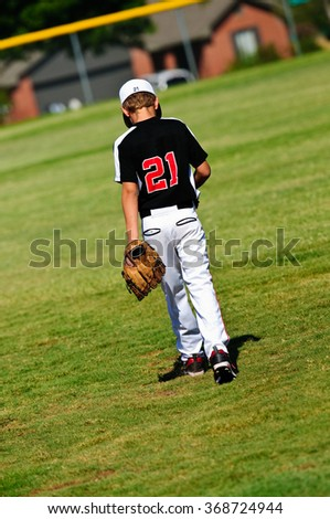 Youth baseball player walking onto the field to get ready to play. - stock photo
