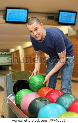 Youth bends over to automat  and takes  ball for playing bowling - stock photo
