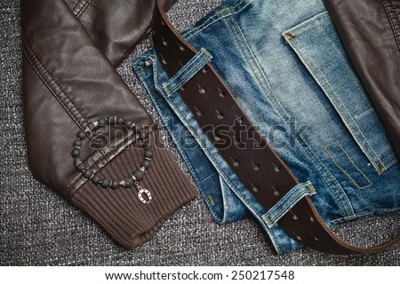 youth clothes: jeans with a leather belt, leather jacket, jewelry bracelet on the arm - stock photo