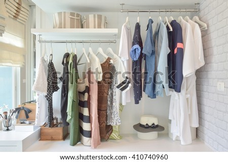 Youth cloths hanging in open wardrobe in the bedroom - stock photo