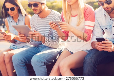 Youth culture. Four young people sitting close to each other and looking at their gadgets