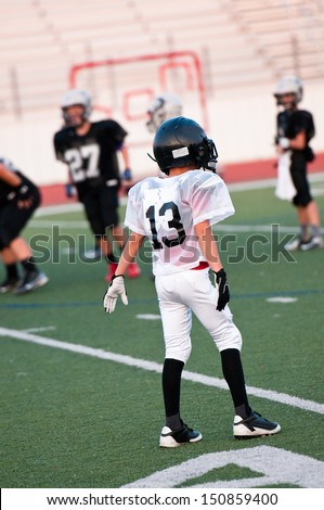 Youth football player on defense - stock photo