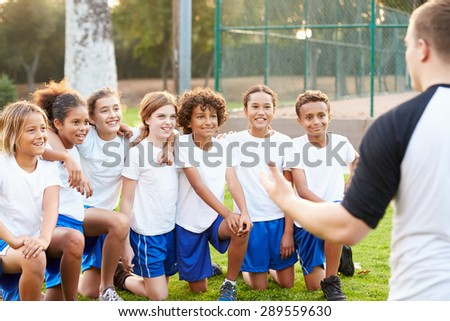 Youth Football Team Training With Coach - stock photo